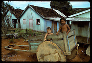 Two little boys play in oxcart parked on dirt road in jungle town of Eirunepe, Amazonas. Brazil