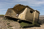 WW2-era concrete pillbox defence structure lies on the beach after coastal erosion at Warden Point, Isle of Sheppey, Kent.