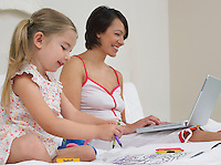 Mother and daughter drawing and using laptop on bed