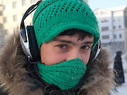 Street portrait of a young Yakutsk inhabitant protected himself with headphones and woolen hat against the extrem cold. Yakutsk is a city in the Russian Far East, located about 4 degrees (450 km) below the Arctic Circle. It is the capital of the Sakha (Yakutia) Republic (formerly the Yakut Autonomous Soviet Socialist Republic), Russia and a major port on the Lena River. Yakutsk is one of the coldest cities on earth, with winter temperatures averaging -40.9 degrees Celsius.