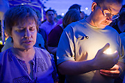 22 SEPTEMBER 2007 -- PHOENIX, AZ: CAROL CONDIT, left, from Phoenix, and DALE ERFLE, from New Salem, N.D. and the brother of Phoenix Police Officer Nick Erfle, hold candles and pray during a vigil for Erfle, who was murdered Tuesday, Sept. 18, when he stopped a man for jaywalking on a Phoenix street. The man, Erik Martinez, was an illegal immigrant with a lengthy criminal history who had been deported from the United States and snuck back in. He was a member of a Mexican gang and wanted on felony assault warrants, which is why he shot Erfle when he was stopped for jaywalking. Martinez carjacked a passing vehicle in an effort to escape but was shot and killed a few miles from where he killed Erfle. Photo by Jack Kurtz / ZUMA Press