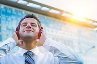 Mature businessman listening on music with headphones on
