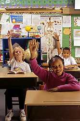 Stock photo of young elementary school students eager to answer questions