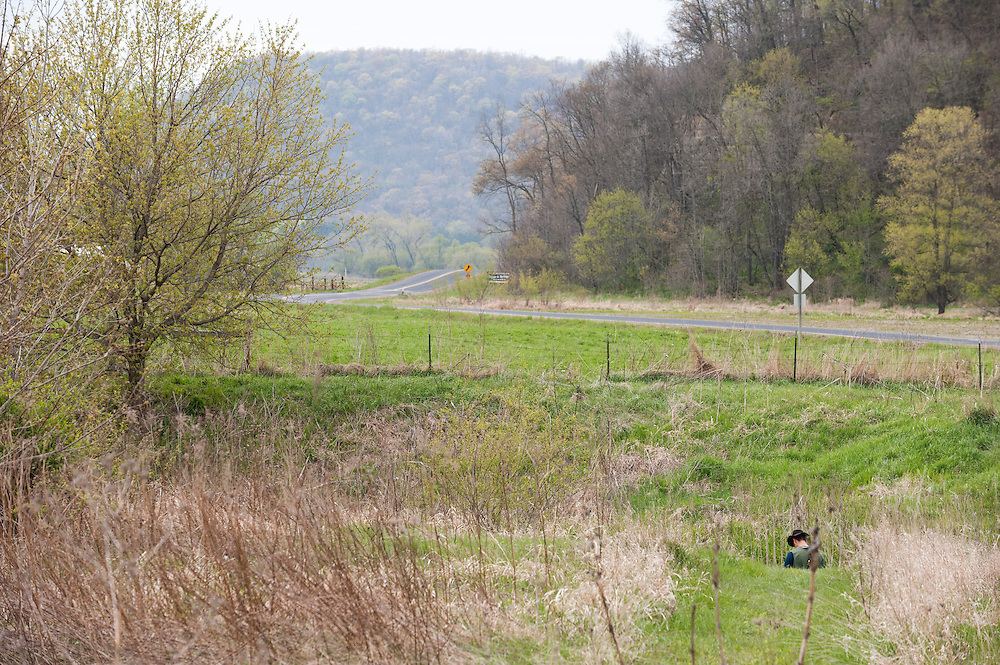 An angler's head is visible in the landscape of Wisconsin's Driftless Area as he fishes a tributary to the Timber Coulee creek.