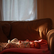 A three month old baby girl lies content on the couch as the early morning sunlight streams through the window. Photo Tim Clayton