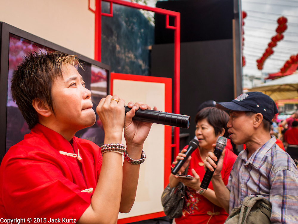 "19 FEBRUARY 2015 - BANGKOK, THAILAND: A woman sings karaoke on Yaowarat Road during Chinese New Year festivities in the Chinatown neighborhood of Bangkok. 2015 is the Year of Goat in the Chinese zodiac. The Goat is the eighth sign in Chinese astrology and ""8"" is considered to be a lucky number. It symbolizes wisdom, fortune and prosperity. Ethnic Chinese make up nearly 15% of the Thai population. Chinese New Year (also called Tet or Lunar New Year) is widely celebrated in Thailand, especially in urban areas that have large Chinese populations.    PHOTO BY JACK KURTZ"