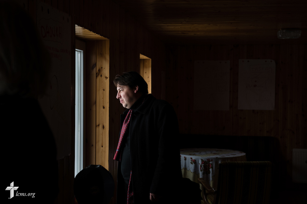 The Rev. Mindaugas Kairys peers from the window at the Diaconia daycare center under the Evangelical Lutheran Church in Lithuania on Friday, Feb. 6, 2015, in rural Skirsnemune, Lithuania. LCMS Communications/Erik M. Lunsford