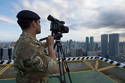 Second Lieutenant Ash Badwaj films the Manila skyline from the roof of the Discovery Suites Hotel.<br /> 24/04/2015.<br /> <br /> Credit should read: Cpl Mark Larner RY<br /> <br /> Exercise Civil Bridge is being conducted by elements of 77 Brigade &ndash; a specialist British military unit that is working alongside the government and disaster relief organisations as part of an annual overseas training exercise. <br /> <br /> Their mission during the two-week deployment will be to look at examples of the existing Philippine earthquake contingency response plans and, working with Philippine colleagues, make suggestions that will help save lives by enhancing the country&rsquo;s ability to respond to an earthquake in an urban setting.