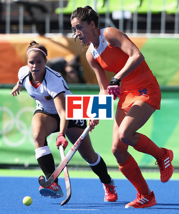 RIO DE JANEIRO, BRAZIL - AUGUST 13:  Naomi van As of the Netherlands moves away from the Pia Sophie Oldhafer during the Women's group A hockey match between the Netherlands and Germany on Day 8 of the Rio 2016 Olympic Games at the Olympic Hockey Centre on August 13, 2016 in Rio de Janeiro, Brazil.  (Photo by David Rogers/Getty Images)