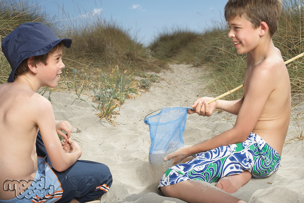 Two boys (6-11) in sand dunes playing with fishing net