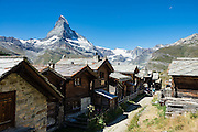 In Findeln (Findelen), admire the Matterhorn and authentic Walser houses, barns, and stores built of larch timber blackened by the sun, above Zermatt, in the Pennine Alps, Switzerland, Europe. The Walser people are named after Wallis (Valais), the uppermost Rhône valley, where they settled from the 900s in the late phase of the migration of the Alamanni (confederation of Germanic tribes) crossing from the Bernese Oberland. From Zermatt, hike the Five Lakes Trail from Sunnegga Express funicular. Although especially nice for families, the 5-Seenweg loop walk is aesthetically marred with ski slope infrastructure throughout (5 dammed artificial lakes, power lines, lifts, dusty roads, snow-making sprinklers, etc). Visually, the most aesthetic features are the old wood buildings in upper Findeln, and the reflecting lakes of Grindjisee and Stellisee.