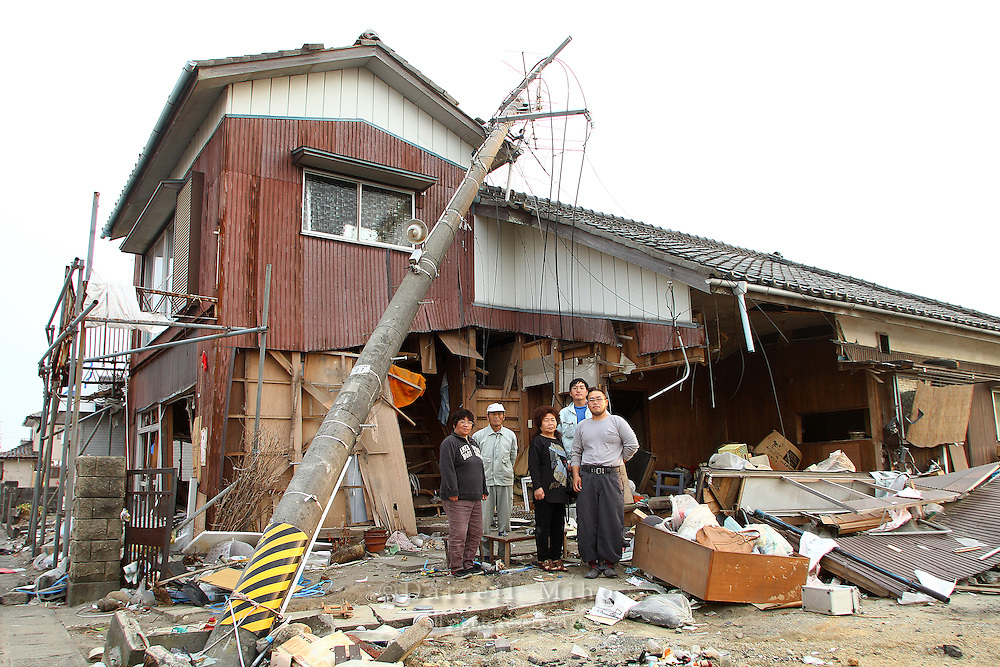 May 16, 2011; Watari, Miyagi Pref., Japan - The Shishido family poses in front of what is left of their house after the magnitude 9.0 Great East Japan Earthquake and Tsunami that devastated the Tohoku region of Japan on March 11, 2011...They have been coming to their house almost everyday, but this was the last day they can take anything out as their house was scheduled for demolition the next day.