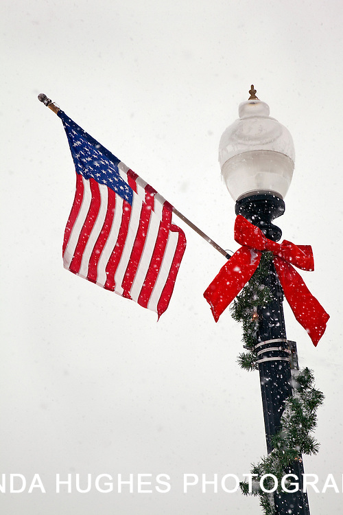 Lamp Post in a snow storm at Christmas with a US flag