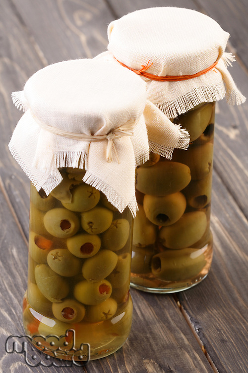 Pickled olives in jar on wooden table