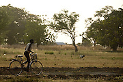 A child rides a bike along a country dirt road.