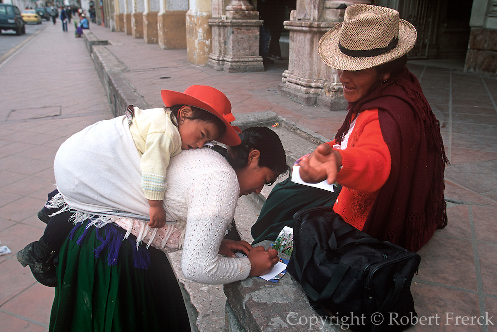 ECUADOR, HIGHLANDS, CUENCA indian women with child write postcard