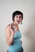 Studio shot of a female model in her 20s doing the OK sign on white background