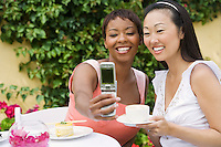 Women photographing themselves at outdoor table