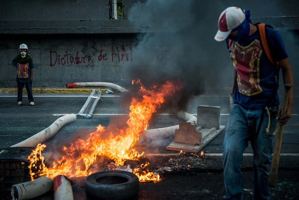 "CARACAS, VENEZUELA - MAY 26, 2017:  Anti-government protesters construct a roadblock next to graffiti that says, ""Dictatorship of Hunger"", after taking control of the main highway that runs through Caracas. The streets of Caracas and other cities across Venezuela have been filled with tens of thousands of demonstrators for nearly 100 days of massive protests, held since April 1st. Protesters are enraged at the government for becoming an increasingly repressive, authoritarian regime that has delayed elections, used armed government loyalist to threaten dissidents, called for the Constitution to be re-written to favor them, jailed and tortured protesters and members of the political opposition, and whose corruption and failed economic policy has caused the current economic crisis that has led to widespread food and medicine shortages across the country.  Independent local media report nearly 100 people have been killed during protests and protest-related riots and looting.  The government currently only officially reports 75 deaths.  Over 2,000 people have been injured, and over 3,000 protesters have been detained by authorities.  PHOTO: Meridith Kohut"
