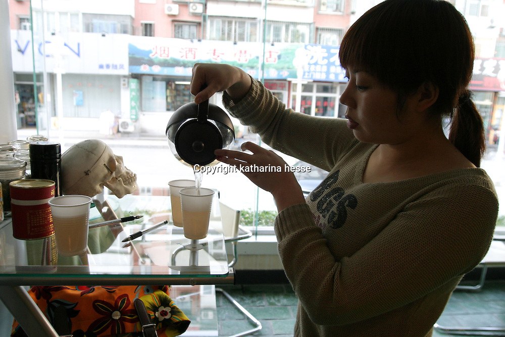 "BEIJING, 12.October 2004: Meng Ge, 24, pours tea for potential patients ina hospital for plastic surgery in Beijing, October 12, 2004, in China. Meng herself will undergo plastic surgery in a few days in order to improve her appearance. Gu dislikes her round face and and eyes. As she cannot afford the surgery out of her own pocket, she decided to become a consultant in the hospital  for plastic surgery whose director offered to pay for her surgery provided she'd stay on ... ..Plastic surgery gradually is becoming big business in China's capital.  Since this summer , hospitals  have been flooded with teenage patients ever since offers ""special summer reductions"" for students were made..  ..Whereas in Mao Zedong's China, even pigtails were seen as a sign of vanity (and had to be cut off) , nowadays, urban Chinese women seek about every means in order to distinguish themselves from the masses.  This year Beijing will organize the worl'd first beauty pageant for women had had plastic surgery..."