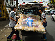 10 AUGUST 2016 - BANGKOK, THAILAND: Men put a portrait of Queen Sirikit into a car in central Bangkok. The portrait was bought for display on the Queen's Birthday. Thais are preparing for the Queen's birthday. Queen Sirikit of Thailand, was born Mom Rajawongse Sirikit Kitiyakara on 12 August 1932. She married  Bhumibol Adulyadej, King of Thailand (Rama IX) in 1950. He is the longest serving monarch in the world and she is longest serving consort of a monarch. Her birthday, like the King's Birthday (which falls on Dec. 5),  is a national holiday in Thailand. Her birthday, August 12, is also celebrated as Mothers' Day in Thailand. Thais hang portraits of Queen Sirikit in their homes and fly her royal flag on her birthday.        PHOTO BY JACK KURTZ