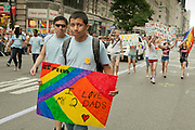 "A young man carrying a sign saying ""I love 2 Dads"" marching with PFLAG NYC in the 2011 Pride Parade on New York's Fifth Avenue."