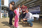 Left to right, Beatriz Navarrete watches as Vanessa Navarrete, 4, both of Carthage, Mo., talk with Naturally Blue PAC co-founders and CEO, Will Whiting, communications director, Marc Peters, and President, Nate Looney, on Saturday, March 17, 2012 at Bulldog Stadium in Springdale, Ark. (Photo by Beth Hall)