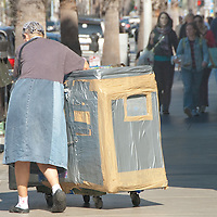 A homeless woman pushes her hand-made home near the Third Street Promenade on Friday, October 22, 2010.
