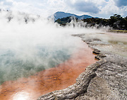 Steam rises from orange and green Champagne Pool at Wai-O-Tapu Thermal Wonderland, North Island, New Zealand