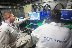Technicians testing the computer systems in The Operations Room. Tour of the Queen Elizabeth Aircraft Carrier under construction at the Babcock site in Rosyth dockyard.