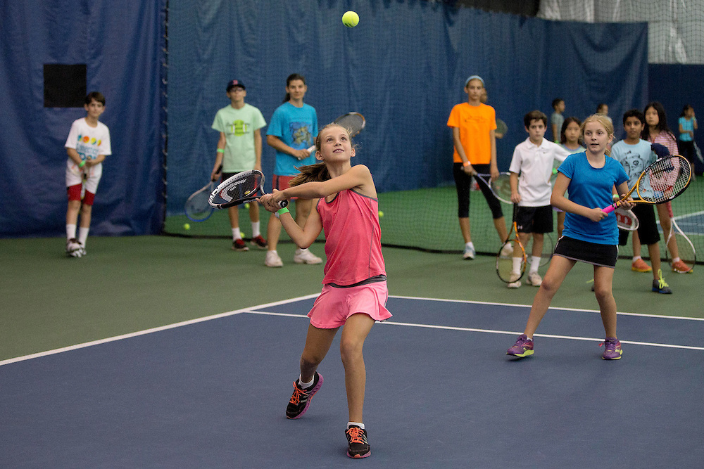 August 16, 2014, New Haven, CT:<br /> A young fan hits a tennis ball during a tennis clinic as part of Kids Day on day three of the 2014 Connecticut Open at the Yale University Tennis Center in New Haven, Connecticut Sunday, August 17, 2014.<br /> (Photo by Billie Weiss/Connecticut Open)