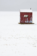 A red ice-fishing hut in a snow storm on Eagle lake, Acadia National Park, Maine.