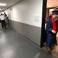 Hunter Foster walks out of a dressing room with classmate Kyle Tigrett after getting ready for the Nettleton High School graduation ceremony on Saturday morning.
