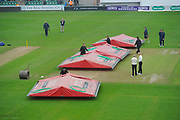 The umpires stand and watch next to the wicket as the covers begin to be removed before the second day of the Specsavers County Champ Div 1 match between Somerset County Cricket Club and Middlesex County Cricket Club at the Cooper Associates County Ground, Taunton, United Kingdom on 26 September 2017. Photo by Graham Hunt.