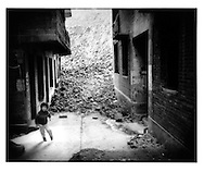 Boy playing amidst demolition rubble flowing into alleyway where the last remaining residents of Fengdu still live.  Most of the building are unoccupied and gutted.  Three Gorges of the Yangtze River, China.