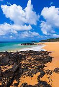 Surf and lava rock at Secret Beach, North Shore, Island of Kauai, Hawaii USA