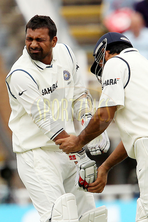 MS Dhoni assists Praveen Kumar after he was hit by a delivery during day four of the third test match between England and India held at Edgbaston Cricket ground in Birmingham on the 13th August 2011...Photo by Ron Gaunt/SPORTZPICS/BCCI