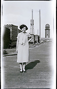 female person with in the background a timber mill USA 1920s