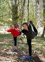 Phoebe VanScoy-Giessler and Kate Kretschmer in standing bow pose during Kretschmer's Trail Yoga at Prescott Farm Environmental Education Center on Saturday morning.  (Karen Bobotas/for the Laconia Daily Sun)