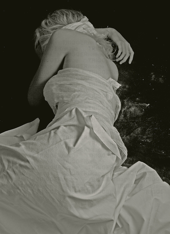 A young woman with blonde hair wearing a white dress lying on the floor