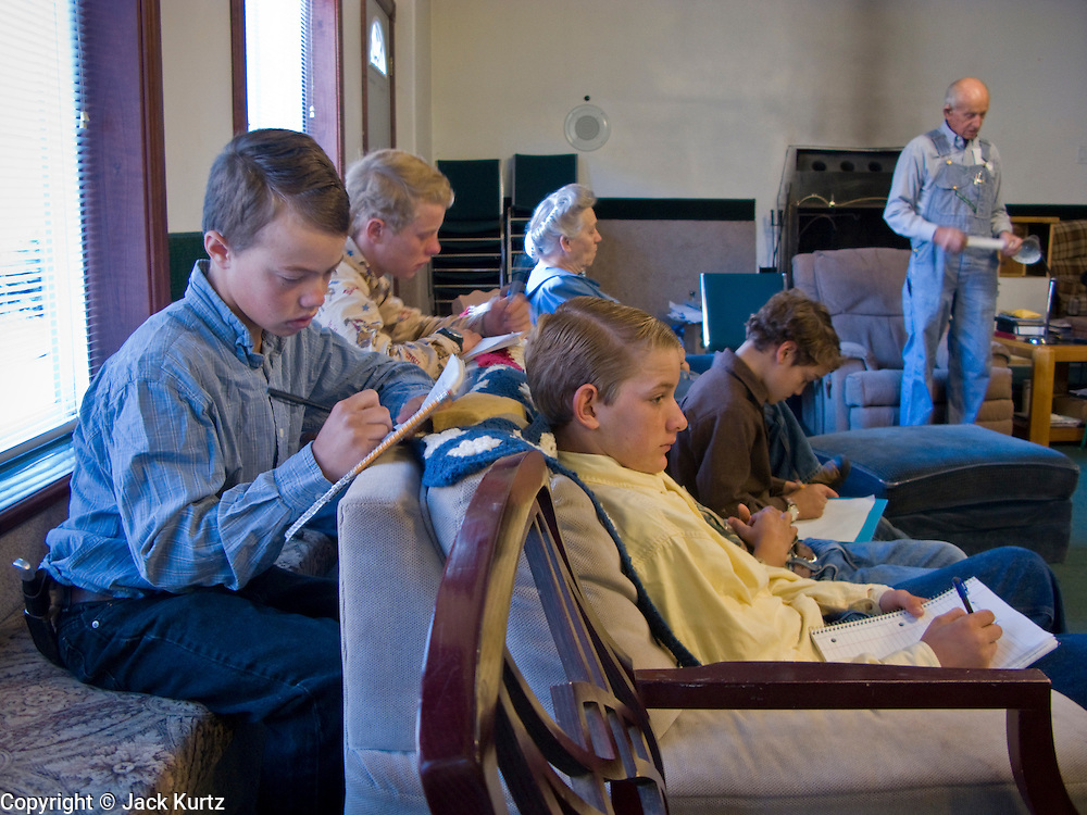 "Sept 8, 2008 -- COLORADO CITY, AZ: Boys in the Jessop family finish their homework during morning prayers before home schooling starts. Members of the FLDS pulled their children from the public schools several years ago, now most of the families in town home school their children. The Jessops have almost 40 youngsters, in grades kindergarten through 8th grade, in their home school. Colorado City and the neighboring town of Hildale, UT, are home to the Fundamentalist Church of Jesus Christ of Latter Day Saints (FLDS) which split from the mainstream Church of Jesus Christ of Latter Day Saints (Mormons) after the Mormons banned what they call ""Celestial Marriage"" (polygamy) in 1890 so that Utah could gain statehood into the United States. The FLDS Prophet (leader), Warren Jeffs, has been convicted in Utah of ""rape as an accomplice"" for arranging the marriage of teenage girl to her cousin and is currently on trial for similar, those less serious, charges in Arizona. After Texas child protection authorities raided the Yearning for Zion Ranch, (the FLDS compound in Eldorado, TX) many members of the FLDS community in Colorado City/Hildale fear either Arizona or Utah authorities could raid their homes in the same way. Older members of the community still remember the Short Creek Raid of 1953 when Arizona authorities using National Guard troops, raided the community, arresting the men and placing women and children in ""protective"" custody. After two years in foster care, the women and children returned to their homes. After the raid, the FLDS Church eliminated any connection to the ""Short Creek raid"" by renaming their town Colorado City in Arizona and Hildale in Utah. The Jessops are a polygamous family and members of the FLDS.   Photo by Jack Kurtz / ZUMA Press"