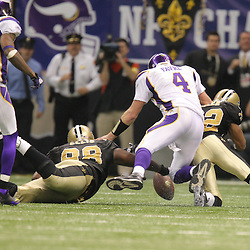 Jan 24, 2010; New Orleans, LA, USA; Minnesota Vikings quarterback Brett Favre (4) and New Orleans Saints defensive tackle Sedrick Ellis (98) and cornerback Tracy Porter (22) scramble for a fumble during a 31-28 overtime victory by the New Orleans Saints over the Minnesota Vikings in the 2010 NFC Championship game at the Louisiana Superdome. Mandatory Credit: Derick E. Hingle-US PRESSWIRE