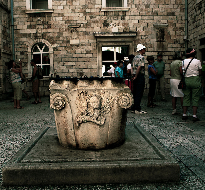 Medieval well head, in a regional Venetian Byzantine style, in a courtyard in Trogir, Croatia.  Corner volutes and a relief panel of the winged lion of St. Mark.