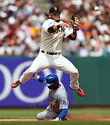 San Francisco Giants shortstop Brandon Crawford leaps over Los Angeles Dodgers' Jimmy Rollins to complete a double play during the eighth inning of a baseball game, Thursday, May 21, 2015, in San Francisco. (AP Photo/Beck Diefenbach)
