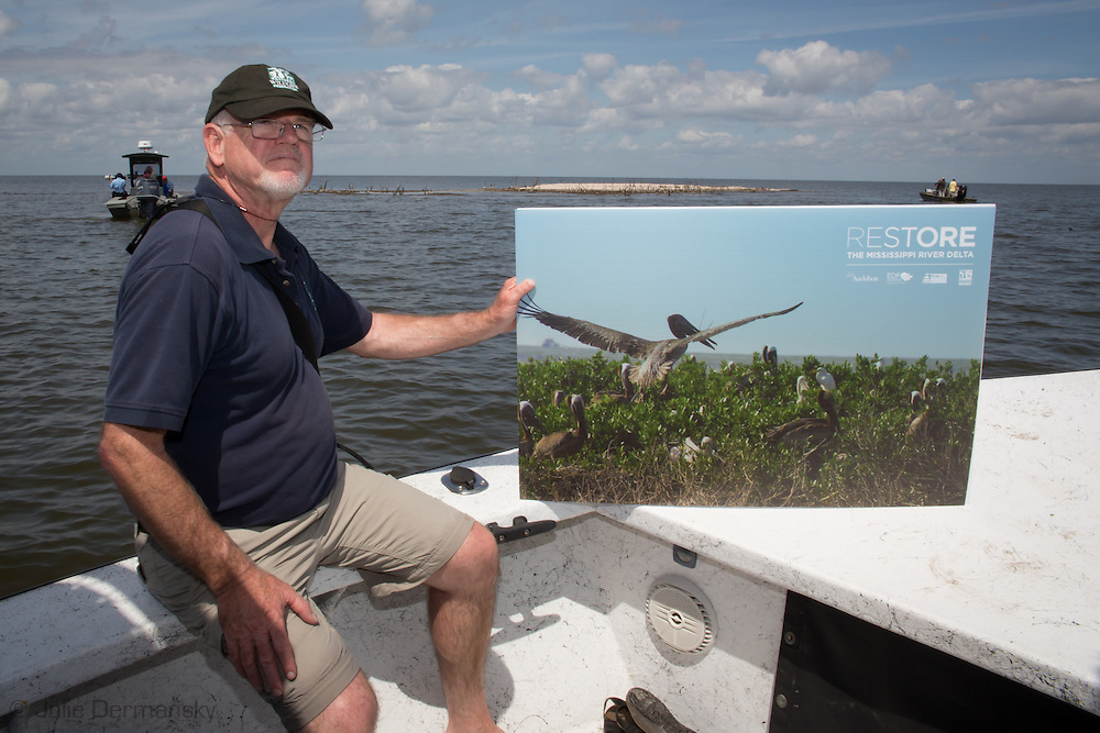 March 31, 2015,   David Muth, Gulf Coast restoration director for the National Wildlife Federation in  holds up a photo of what  Cat Island, a barrier island in Plaquemines Parish looked like before the BP oil spill, behind him, the remains of the island, 5 years after the spill.