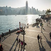 China, Hong Kong, Shadows cast by couples walking along waterfront promenade in Tsim Sha Tsui on Kowloon Peninsula at sunset on winter evening