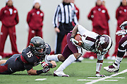 LITTLE ROCK, ARKANSAS - NOVEMBER 23:  Price Holmes #15 of the Arkansas Razorbacks tackles Jameon Lewis #4 of the Mississippi State Bulldogs at War Memorial Stadium on November 23, 2013 in Little Rock, Arkansas.  The Bulldogs defeated the Razorbacks 24-17.  (Photo by Wesley Hitt/Getty Images) *** Local Caption *** Price Holmes; Jameon Lewis