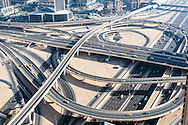 Motorway interchange between Sheikh Zayed Road 12 lane highway and Financial Center Road of Downtown Dubai. Dubai metro train elevated flyover crosses above the many major roads.