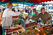 Frenchman serving customer at fruit staff at food market at Esplanade  des Quais in La Reole, Bordeaux region, France
