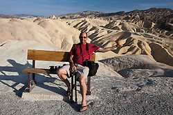 Adult male sits on park bench in front of the badlands at Zabriskie Point, Death Valley National Park, California, United States of America